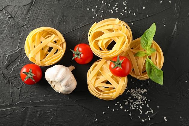 Composizione con pasta, pomodori, sale e aglio su sfondo nero, spazio per il testo