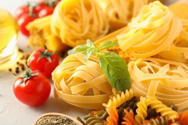 Composizione con pasta, i pomodori, le spezie e l'olio d'oliva su fondo bianco, primo piano