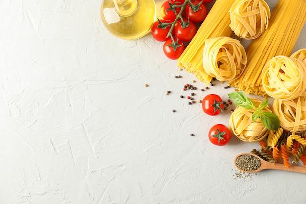 Composizione con pasta, pomodori, spezie e olio d'oliva su sfondo bianco, spazio per il testo