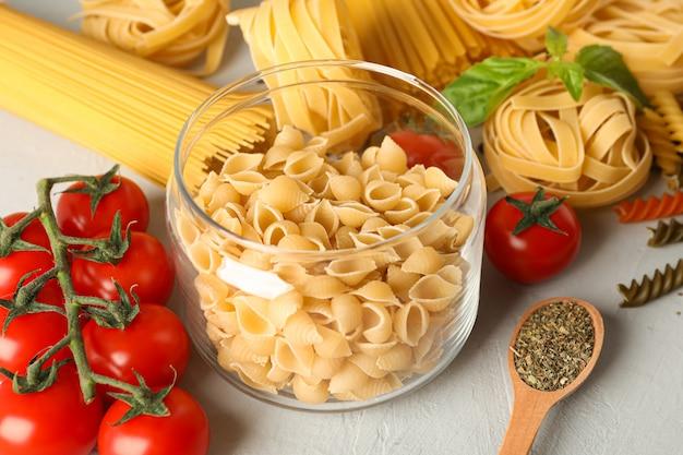 Composizione con pasta, pomodori e spezie su sfondo bianco, spazio per il testo