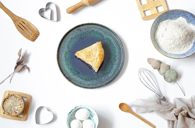 Composizione con un pezzo di torta su un piatto e ingredienti per cucinare e accessori per la cucina sul tavolo bianco.