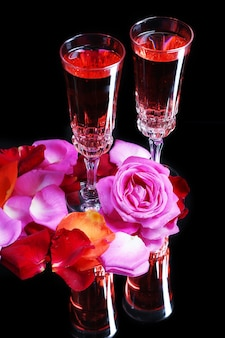 Composizione con vino rosa in bicchieri, bottiglia e rose sul nero