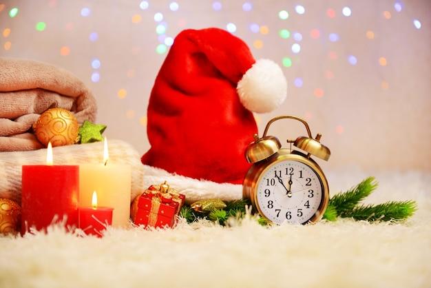 Composizione con plaid, candele e addobbi natalizi, su moquette bianca su sfondo luminoso