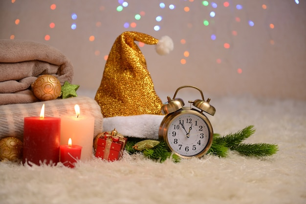 Composizione con plaid, candele e decorazioni natalizie, su tappeto bianco su sfondo luminoso