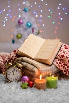 Composizione con plaid, candele e decorazioni natalizie, su tappeto bianco su parete luminosa