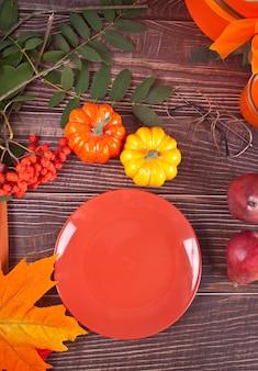 Composizione con piatto, zucca, foglie di autunno, candela e pere rosse sul tavolo di legno, piatto laici
