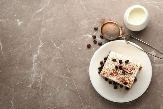 Composizione con piatto di tiramisù su sfondo marrone chiaro. dessert gustoso