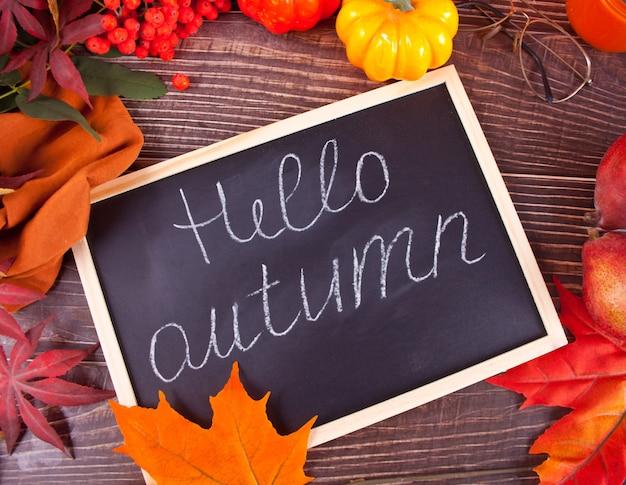 Composizione con zucca, foglie di autunno, cadle e pere rosse su legno, piatto laici