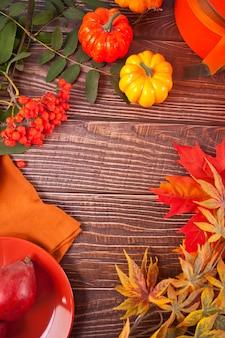 Composizione con zucca, foglie di autunno, candela e pere rosse sul tavolo di legno, piatto laici