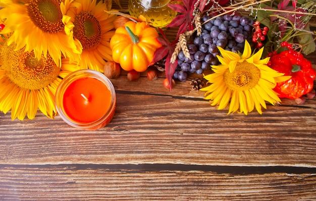 Composizione con zucca, foglie di autunno, uva, girasole, candela e frutti di bosco sul tavolo di legno