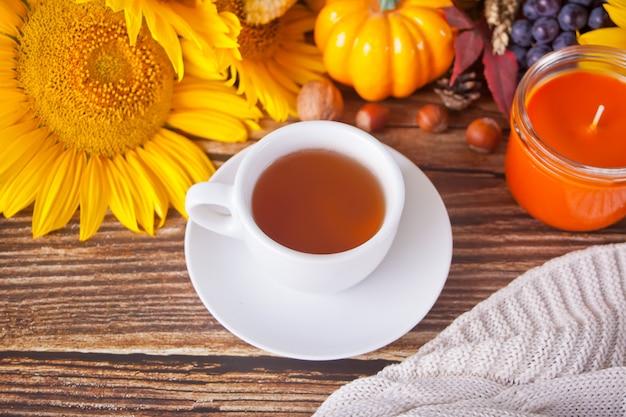 Composizione con zucca, foglie di autunno, girasole, tazza di tè, plaid e bacche sul tavolo di legno
