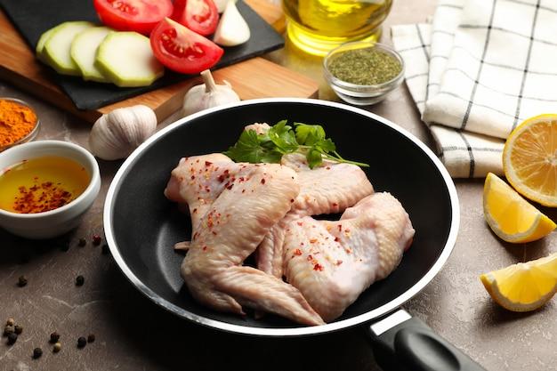 Composizione con pollo crudo e spezie su grigio. cucinare il pollo