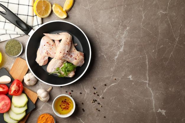 Composizione con pollo crudo e spezie su spazio grigio. cucinare il pollo