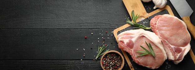 Composizione con carne cruda per bistecca e spezie sulla tavola di legno