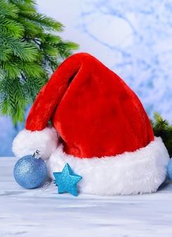 Composizione con cappello rosso di babbo natale e decorazioni natalizie su sfondo chiaro