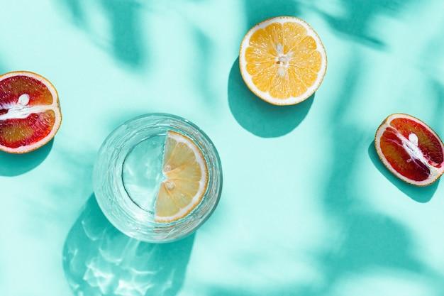 Composizione con fette di pompelmo, arancia rossa, limone e bicchiere di bevanda su sfondo color turchese. l'ora legale era piatta con la luce del giorno.