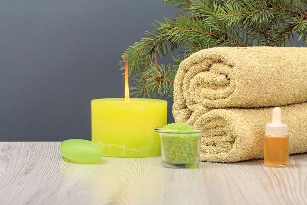 Composizione con un morbido asciugamano in spugna, una bottiglia con olio aromatico, sapone, una ciotola con sale marino, una candela accesa e un ramo di abete sullo sfondo grigio