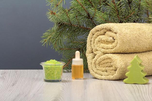 Composizione con un morbido asciugamano in spugna, sapone, una bottiglia con olio aromatico, una ciotola con sale marino e un ramo di abete sullo sfondo grigio
