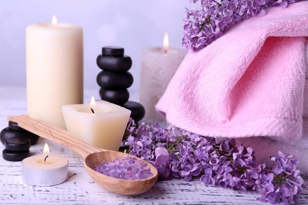 Composizione con trattamento termale, asciugamani e fiori lilla, accesi