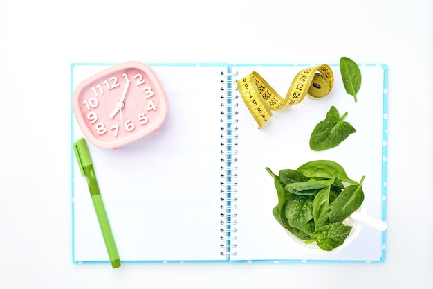 Composizione con spinaci, metro a nastro, taccuino di carta bianca e sveglia rosa sul tavolo bianco. concetto di dieta, copia dello spazio