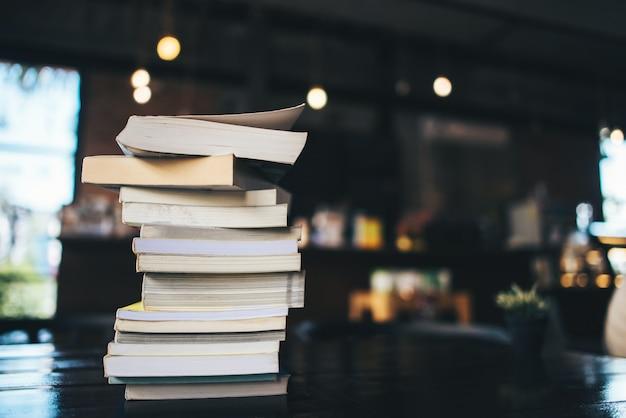 Composizione con la pila di libri sul tavolo nella caffetteria