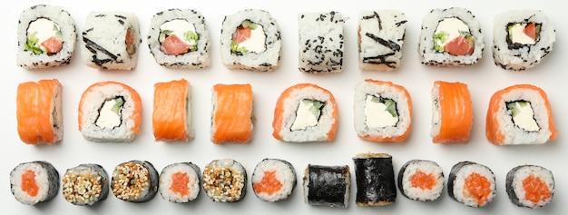 Composizione con i rotoli di sushi su superficie bianca. cibo giapponese