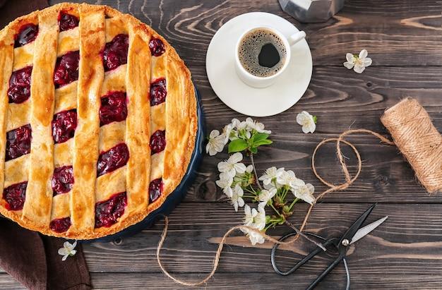 Composizione con gustosa torta di ciliegie e tazza di caffè sulla tavola di legno
