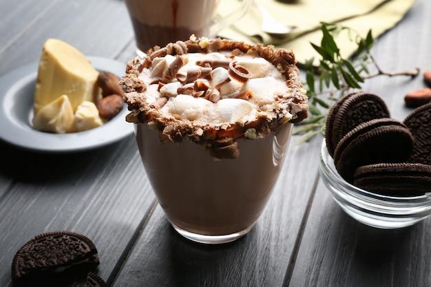 Composizione con gustosa bevanda al cacao su tavola di legno