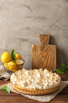 Composizione con torta di meringa al limone gustosa sulla tavola di legno