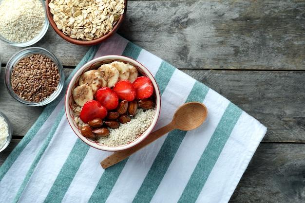 Composizione con gustosa farina d'avena e diversi condimenti su tavola di legno