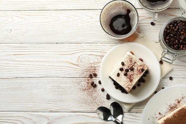 Composizione con gustoso tiramisù su fondo di legno bianco. delizioso dessert