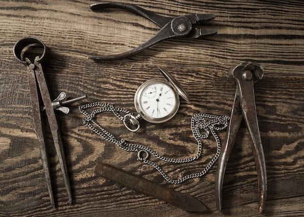Composizione con orologio da tasca vintage, vecchi strumenti arrugginiti e catene