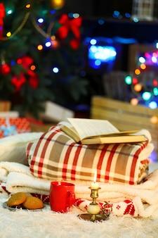 Composizione con plaid caldo, libro, tazza di bevanda calda su sfondo di luci colorate