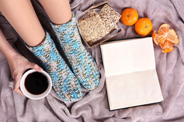 Composizione con plaid caldo, libro, tazza di bevanda calda e gambe femminili, su sfondo tappeto colorato