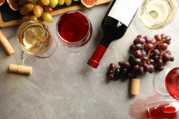 Composizione con vino, uva e cavatappi su sfondo grigio