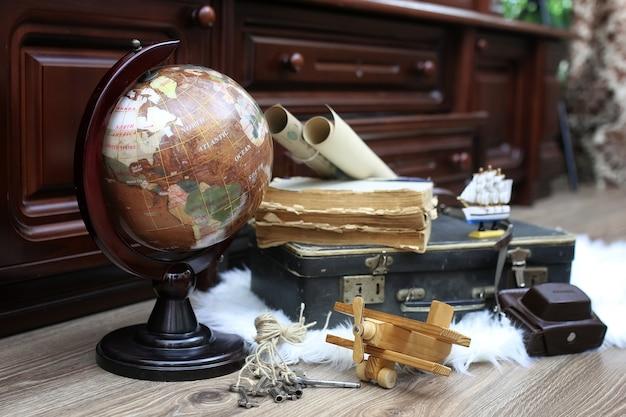 Composizione su pavimento in legno mappamondo vintage con vecchia valigia in pelle con oggetti da viaggio