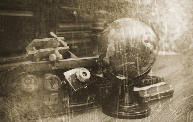 Composizione su pavimento in legno globo vintage con vecchia valigia in pelle con oggetti da viaggio