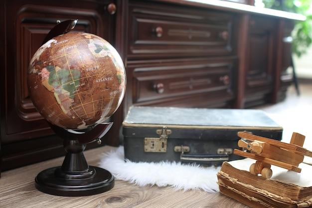 Composizione su pavimento in legno vintage globo con vecchia valigia in pelle con oggetti da viaggio