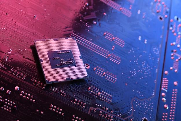 Chip del processore della cpu del computer sul circuito, sfondo della scheda madre. avvicinamento. con illuminazione rosso-blu.