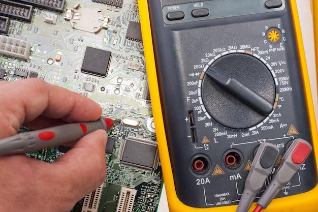 Ingegnere informatico che esamina il circuito della scheda madre con un multimetro
