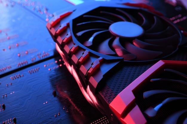 Scheda grafica del gioco per computer, scheda video con due dispositivi di raffreddamento sul circuito, sfondo della scheda madre. avvicinamento. con un'illuminazione rosso-blu.