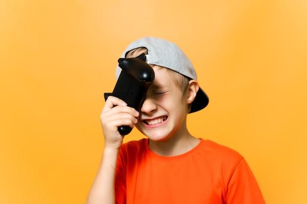 Il ragazzo giocatore di computer appoggiò il gamepad contro la sua testa e fece una smorfia di essere deluso per aver perso la partita