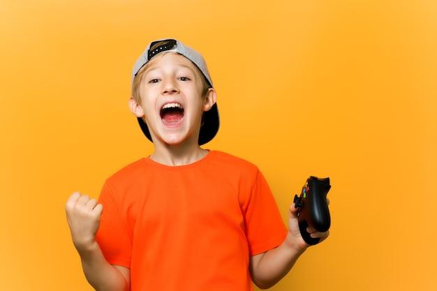 Un ragazzo giocatore di computer su uno sfondo giallo mostra le emozioni. un bambino con un berretto e una maglietta arancione sta giocando a una stazione di gioco