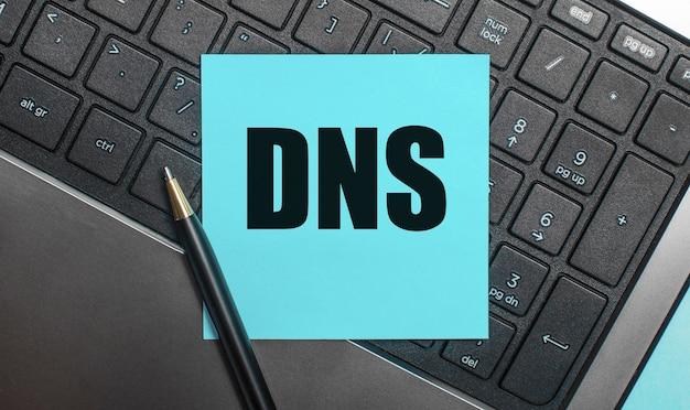 La tastiera del computer ha una penna e un adesivo blu con il testo dns domain name system. disposizione piatta.