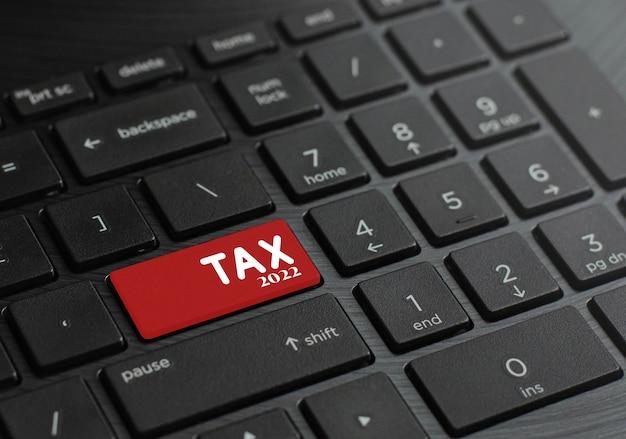 Tastiera del computer con chiavi fiscali nel 2022 per iniziare questo. e imposte detratte dalle entrate e dalle spese nell'anno 2022