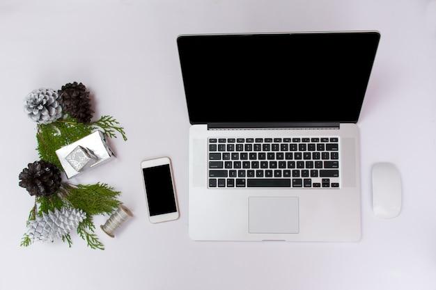 Esposizione mobile del computer portatile del computer sulla tavola con lo schermo bianco isolato per il modello nel natale