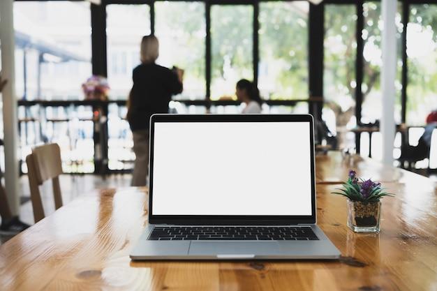 Computer portatile con display bianco sul tavolo di legno in ufficio.