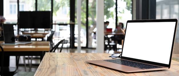 Computer portatile con schermo bianco sulla scrivania in legno.