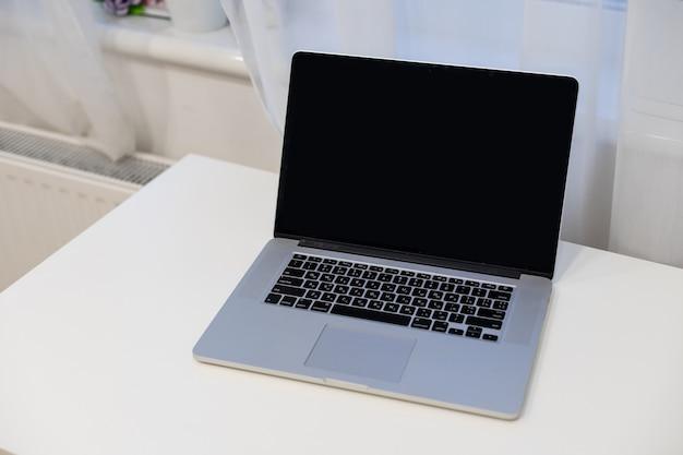Fondo bianco del modello del computer sulla tavola. computer portatile con schermo vuoto. foto di alta qualità