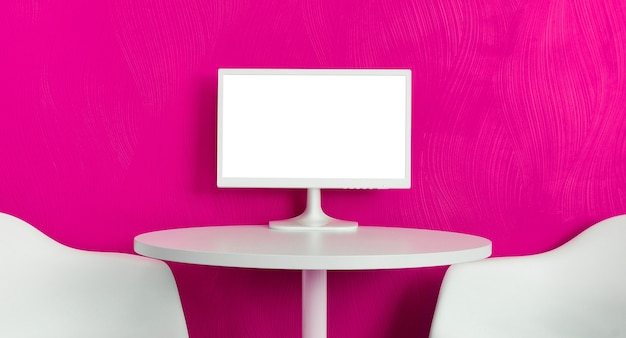 Monitor del computer sul tavolo bianco con due sedie sullo sfondo della parete viola rosa